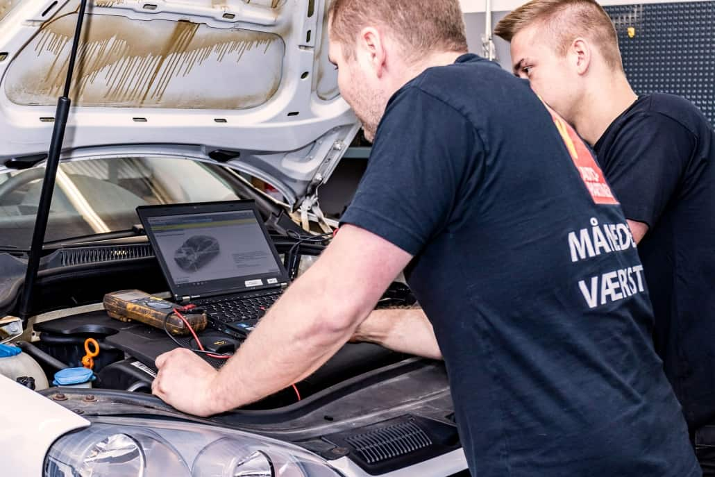 Mekanikere undersøger bil med computer