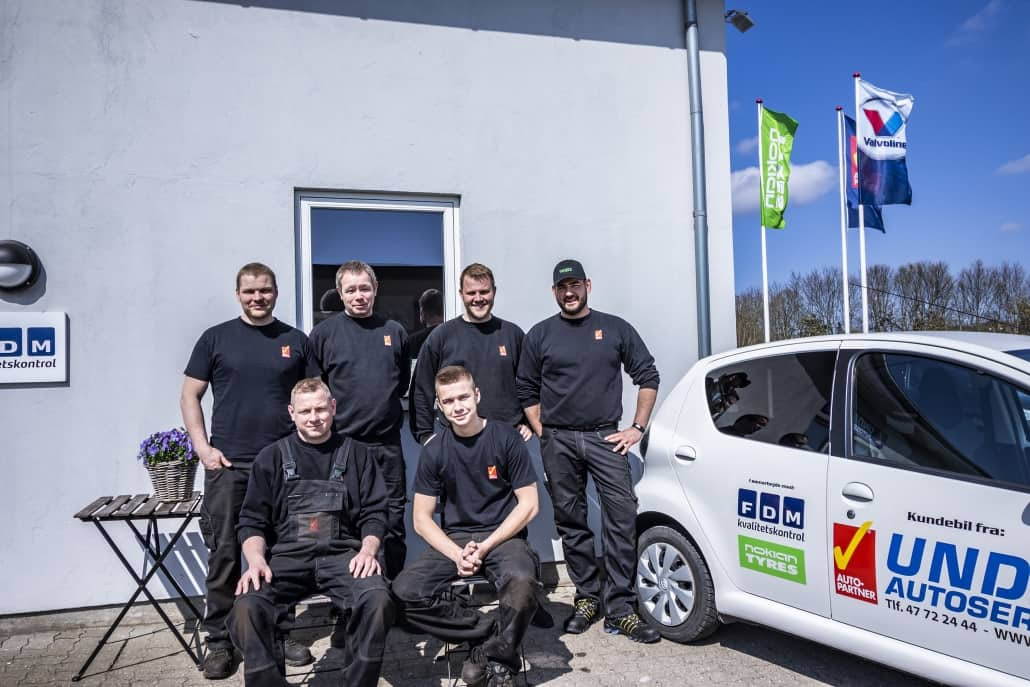 Team portræt foran værksted og reklamebil